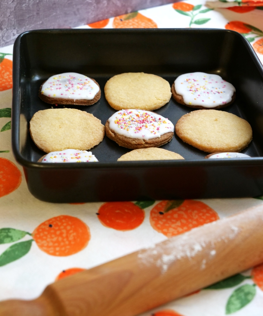 Nine shortbread cookies lie in a baking tin. The tin stands on a colourful table cloth with oranges printed on it. Some of the cookies are glazed and have sprinkles on top.